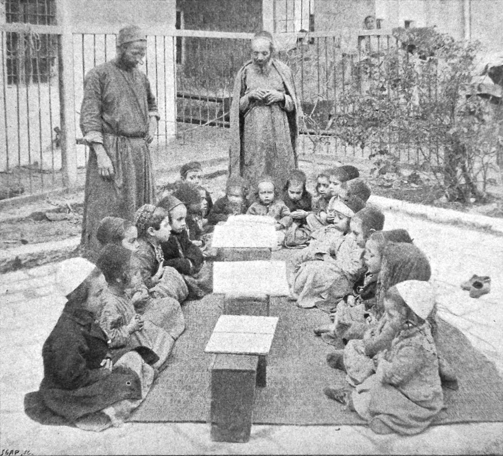 Two rows of boys sitting outdoors on a carpet, facing each other. Male teachers in background.