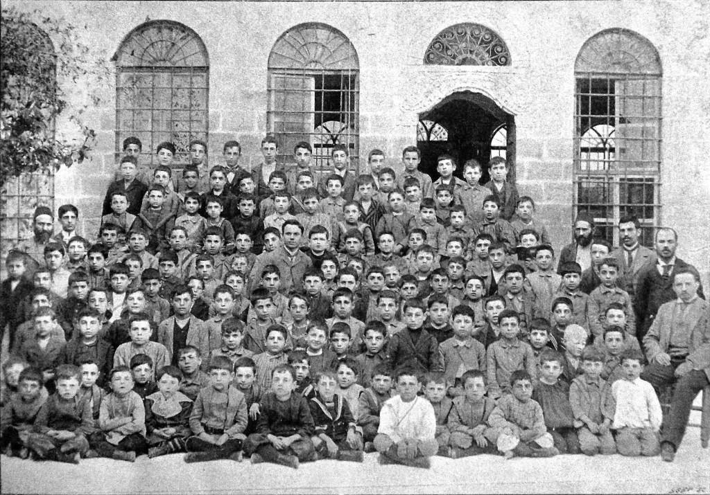 More than 100 students and a few teachers pose for a photo in front of the school.