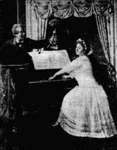 A woman plays the piano as a man holds a lamp over the sheet music.