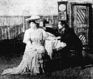 Man and woman seated at a table. He touches her hand and shoulder. She looks away from him.